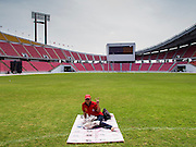 "19 NOVEMBER 2013 - BANGKOK, THAILAND: A Red Shirt protester sits by herself in Rajamangala Stadium before a Red Shirt political rally. As many as 30,000 ""Red Shirts"" are expected in Bangkok this week ahead of a Thai court ruling that could cause the collapse of the government of Yingluck Shinawatra, the Prime Minister. The Red Shirts are gathering in a suburban sports stadium before marching to the court. The Red Shirts are mostly farmers and rural Thais who support the Shinawatra government.      PHOTO BY JACK KURTZ"