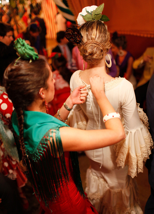 """Abril, 21, 2010. Lifestyle/Spain. Seville April Fair. A crowd of people assists to the """"feria de Abril"""" of Seville. Many women dresses with the traditional costume of """"Flamenca"""" and the people walk,  dance """"sevillanas"""" (typical sevilian dance) and drink """"rebujito"""" (typical drink of the """"Feria de Abril"""" made by the youngdry wine """"Manzanilla""""  and carbonated drink...Una multitud de personas asisten hoy al primer día real de la feria de Abril de Sevilla. Muchas mujeres se visten con el traje tradicional de """"flamenca"""" y pasean por el recinto ferial mientras bailan, beben """"rebujito"""" (bebida típica de la feri de Abril hecha de """"Manzanilla"""" y bebida gaseosa y montan a caballo o en carruaje."""