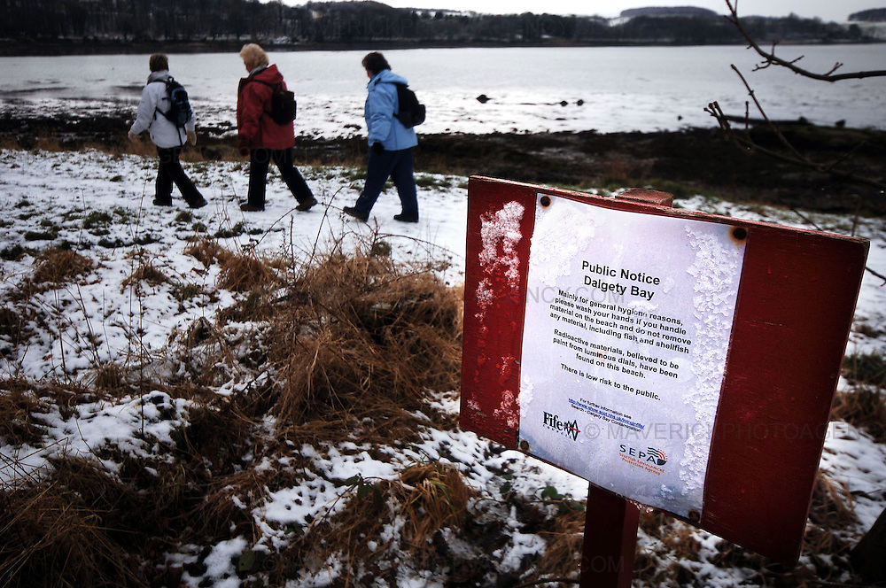 Residents in Dalgety Bay, Fife, are calling for action to clean up a beach contaminated with radioactive particles...The community council said it wants the shoreline cleared by the Ministry of Defence (MOD) within a year...Pic shows three women walk past a sign at Dalgety Bay warning the public about radioactive particles on the beach.