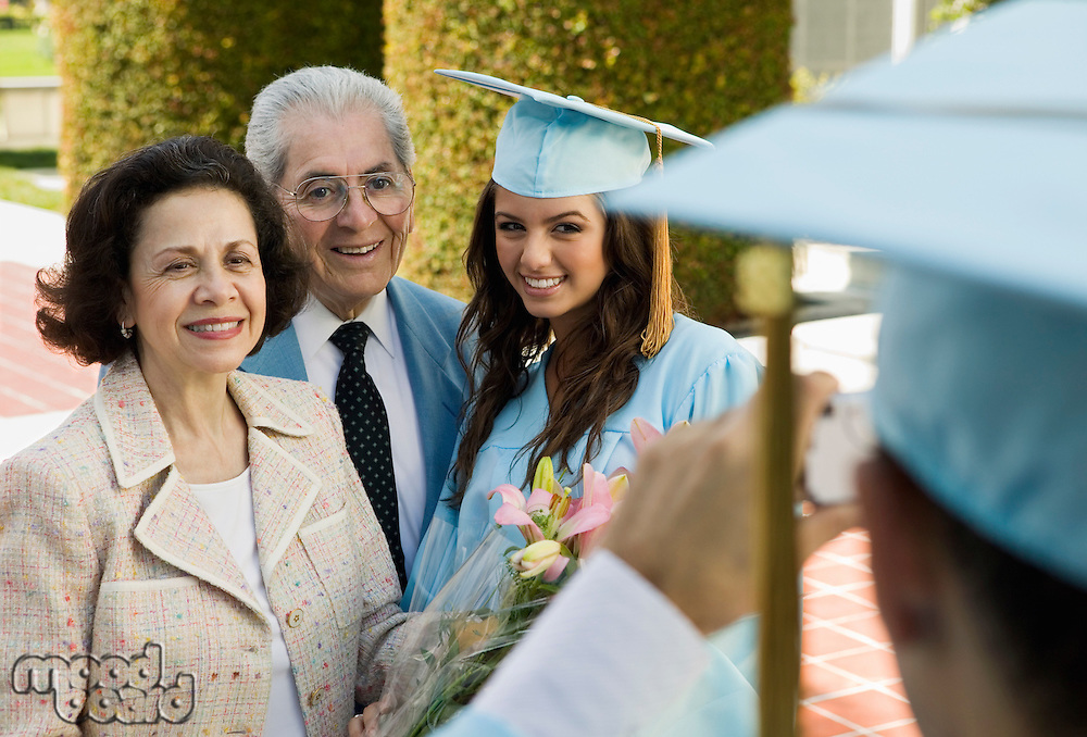Graduate Posing for Picture with Parents