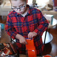 Lauren Wood | Buy at photos.djournal.com<br /> Gabe Shoumaker, 7, plays with one of his toys he received for Christmas at his family's Tupelo home on Christmas day. Gabe and his two sisters were adopted by Mitchell and Dustin Shoumaker from Poland, and they arrived home on Dec. 23, 2015.