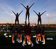 Cheerleaders soar over the landscape at a Knightstown football game.