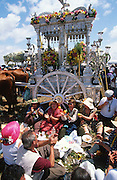 """Singing Sevillanas at a lunch break. The pilgrim route of the Hermandade de Sanlucar de Barrameda from Sanlucar across the Parque Donana to El Rocio, Huelva Province, Andalusia, Spain...El Rocio follows on from Semana Santa - Easter week and the various spring ferias, of which Seville's Feria de Abril (April) is the biggest. The processions to the (Hermitage) Hermita de El Rocío, at Pentecost, is the most famous (Romeria) pilgrimage in the Andalusian region, attracting nearly a million people from across Andalusia, Spain and the world. The cult started off in the 13th century when a statue of the virgin Mary was apparently found in a tree trunk in the Donana Park. What was first a local devotion at Pentecost by local pilgrim brotherhoods """"hermandades"""" became by the 19th century into dozens of fraternities developed from such as Cadiz, Selville and Huelva. Some walk for several days, others travel with oxen drawn wagons or on horseback, with traction engines and all terrain vehicles, camping along the trail they take. They wear Andalusian costumes, tight breeches, boots, short jackets and frilly flamenco skirts. Many festivities, flamenco dance, laments, songs and music are combined with religious prayers. Devout pilgrims walk as a penance, keeping vows of silence. An emblem of the immaculate conception (sin peche) is carried. On the Pentecost after the stroke of midnight on the whit Sunday the virgin Mary is carried from the church through the streets of El Rocio by each hermandade to visit each brotherhood's shrine."""