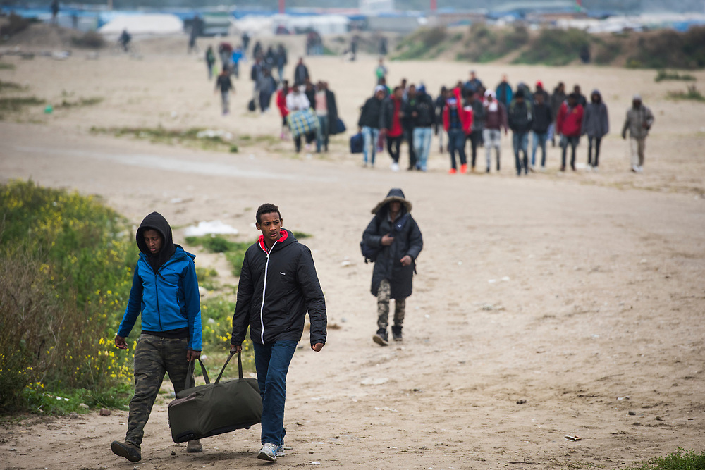 Refugees leave The Jungle refugee camp on October 24, 2016 in Calais, France. Authorities began processing and evicting refugees today; the destruction of the camp is slated to begin tomorrow.