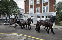 © Licensed to London News Pictures. 29/06/2017. London, UK. The coffin of Grenfell Tower fire victim Tony Disson is carried in a horse drawn hearse to Our Lady of the Holy Souls church for a funeral service in Kensal, West London. Mr Disson is one of only a handful of the 80 victims to have been identified and named so far. Photo credit: Peter Macdiarmid/LNP