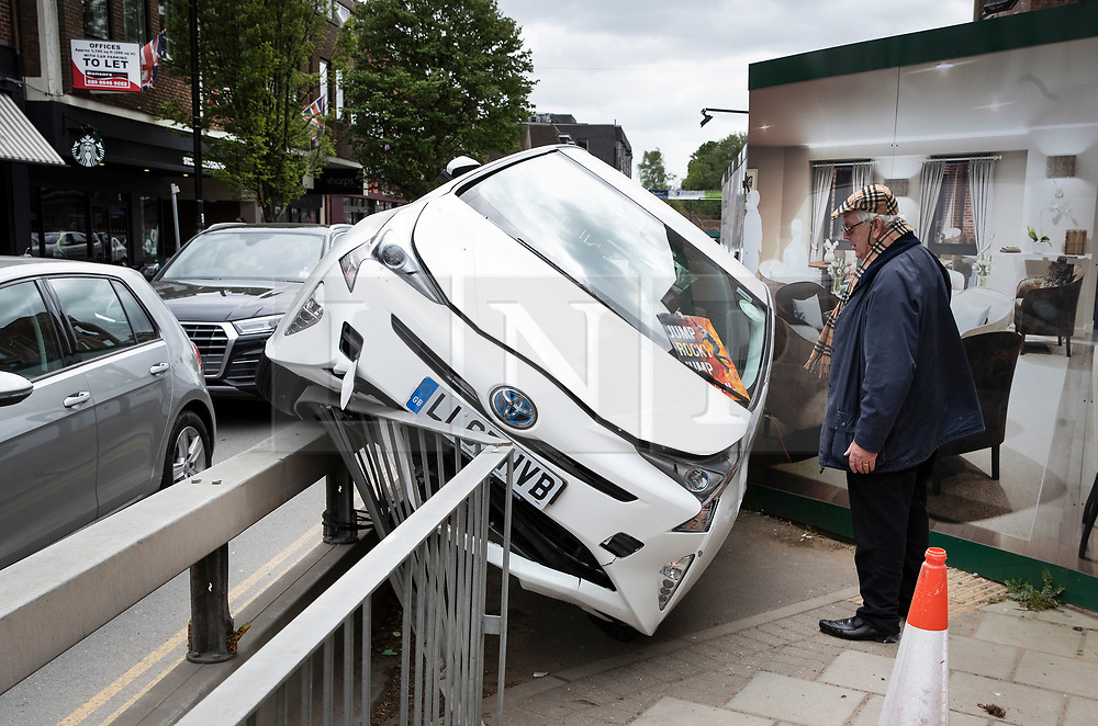 © Licensed to London News Pictures. 27/04/2019. Cobham, UK. A local man inspects a Toyota minicab that has mounted a temporary pedestrian barrier in busy Cobham High Street in Surrey. It is unclear if the driver was affected by high winds and rain from Storm Hannah as he drove the 15-20 meters along the length of the barrier.Photo credit: Peter Macdiarmid/LNP