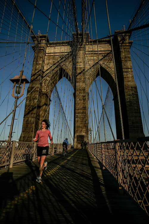 Runner passing in Brooklyn bridge in New York.