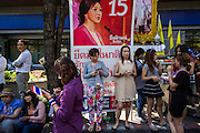 "15 JANUARY 2014 - BANGKOK, THAILAND:  Anti-government protestors lean against campaign posters for Thai Prime Minister Yingluck Shinawatra and her Pheu Thai party during an anti Pheu Thai march in Bangkok. Tens of thousands of Thai anti-government protestors continued to block the streets of Bangkok Wednesday to shut down the Thai capitol. The protest, ""Shutdown Bangkok,"" is expected to last at least a week. Shutdown Bangkok is organized by People's Democratic Reform Committee (PRDC). It's a continuation of protests that started in early November. There have been shootings almost every night at different protests sites around Bangkok. The malls in Bangkok are still open but many other businesses are closed and mass transit is swamped with both protestors and people who had to use mass transit because the roads were blocked.   PHOTO BY JACK KURTZ"