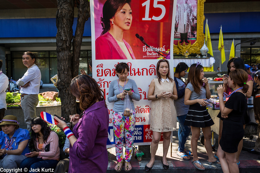 """15 JANUARY 2014 - BANGKOK, THAILAND:  Anti-government protestors lean against campaign posters for Thai Prime Minister Yingluck Shinawatra and her Pheu Thai party during an anti Pheu Thai march in Bangkok. Tens of thousands of Thai anti-government protestors continued to block the streets of Bangkok Wednesday to shut down the Thai capitol. The protest, """"Shutdown Bangkok,"""" is expected to last at least a week. Shutdown Bangkok is organized by People's Democratic Reform Committee (PRDC). It's a continuation of protests that started in early November. There have been shootings almost every night at different protests sites around Bangkok. The malls in Bangkok are still open but many other businesses are closed and mass transit is swamped with both protestors and people who had to use mass transit because the roads were blocked.   PHOTO BY JACK KURTZ"""
