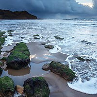 Seaweed Covered Rocks on the Beach and Osgodby Point or Knipe Point Cayton Bay Scarborough North Yorkshire England