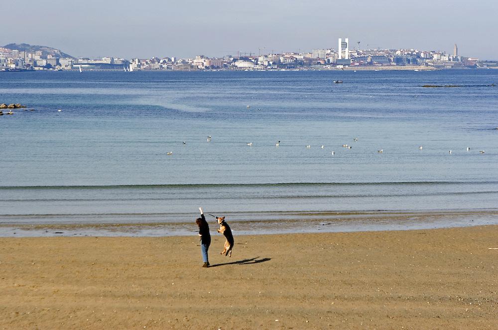 Una joven juega con su perro en la playa de Santa Cruz, con la ciudad de La Coruña el fondo.