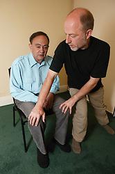 Teacher performing Alexander technique semisupine with patient in treatment room,