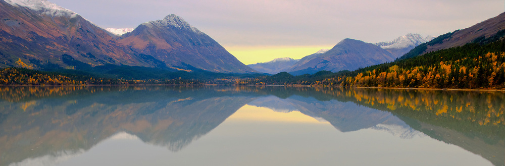 A panoramic view of Trail Lake showing a calm water reflection of the nearby surrounding mountains in fall colors.