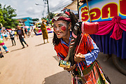 28 JUNE 2014 - DAN SAI, LOEI, THAILAND: A woman with a wooden phallus in the Ghost Festival parade in Dan Sai. Phi Ta Khon (also spelled Pee Ta Khon) is the Ghost Festival. Over three days, the town's residents invite protection from Phra U-pakut, the spirit that lives in the Mun River, which runs through Dan Sai. People in the town and surrounding villages wear costumes made of patchwork and ornate masks and are thought be ghosts who were awoken from the dead when Vessantra Jataka (one of the Buddhas) came out of the forest.     PHOTO BY JACK KURTZ