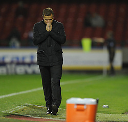 Swindon Town Manager, Mark Cooper brings his hands together near his face after swindon come close to taking the lead. - Photo mandatory by-line: Alex James/JMP - Mobile: 07966 386802 25/08/2014 - SPORT - FOOTBALL - Swindon - County Ground - Swindon Town v Brighton   - League Cup-
