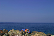 ITALY, Liguria, Camogli: lettura sugli scogli...Italy, Liguria, Camogli: reading and relaxing on the blocks.