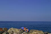 ITALY, Liguria, Camogli: lettura sugli scogli...Italy, Liguria, Camogli: reading and relaxing on the blocks.