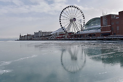© Licensed to London News Pictures. 31/12/2017. CHICAGO, USA.  The ferris wheel on Navy Pier is reflected in ice as the waters of Lake Michigan around Chicago have frozen during a period of sub-zero temperatures.  Extremely cold conditions are forecast to continue into the New Year. Photo credit: Stephen Chung/LNP