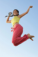 Young woman jumping with mp3 player in hand