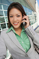 Businesswoman using mobile phone outside office building, portrait