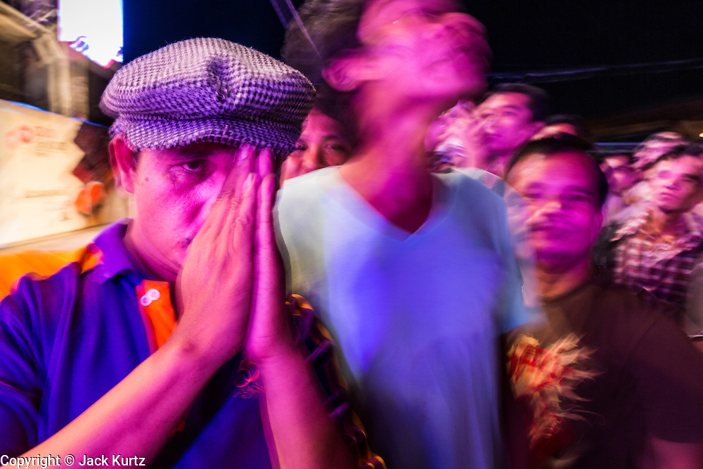 23 NOVEMBER 2013 - BANGKOK, THAILAND: A spectator at a Mor Lam show bows his head during the Thai King's Anthem at the start of the show. Mor Lam is a traditional Lao form of song in Laos and Isan (northeast Thailand). It is sometimes compared to American country music, song usually revolve around unrequited love, mor lam and the complexities of rural life. Mor Lam shows are an important part of festivals and fairs in rural Thailand. Mor lam has become very popular in Isan migrant communities in Bangkok. Once performed by bands and singers, live performances are now spectacles, involving several singers, a dance troupe and comedians. The dancers (or hang khreuang) in particular often wear fancy costumes, and singers go through several costume changes in the course of a performance. Prathom Bunteung Silp is one of the best known Mor Lam troupes in Thailand with more than 250 performers and a total crew of almost 300 people. The troupe has been performing for more 55 years. It forms every August and performs through June then breaks for the rainy season.              PHOTO BY JACK KURTZ