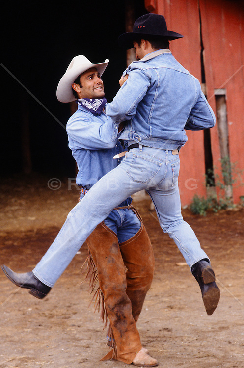 cowboy lifting up another cowboy in midair on a ranch