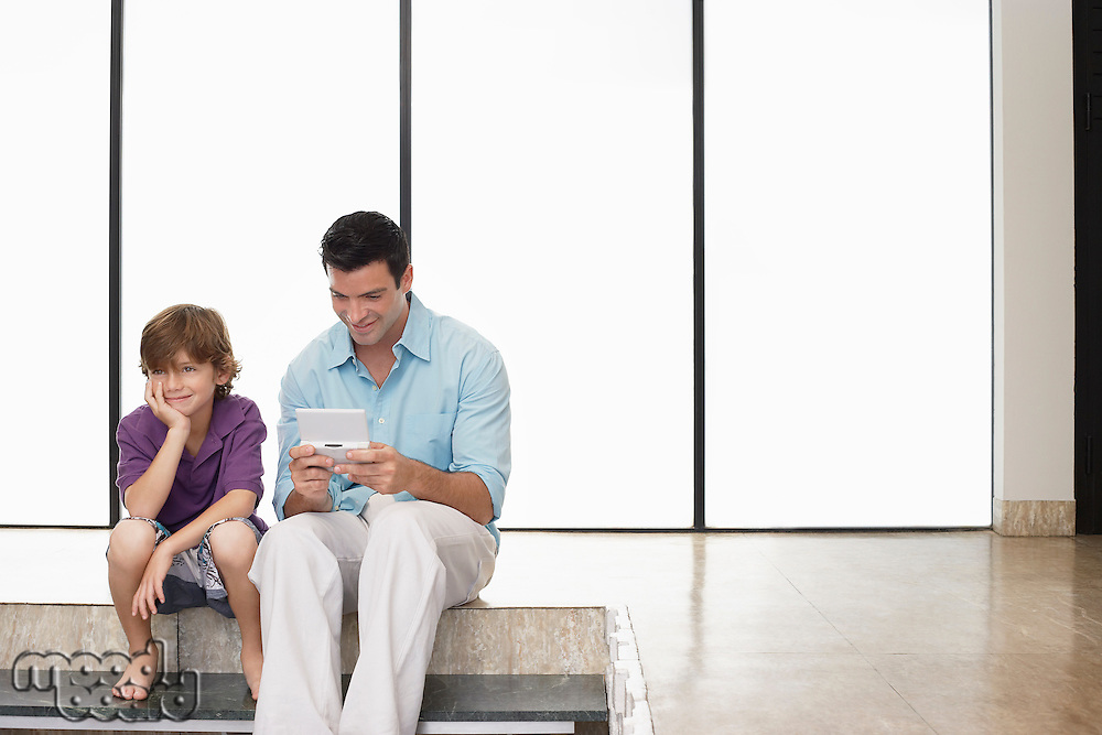 Father and son (7-9) sitting on floor indoors man playing handheld game