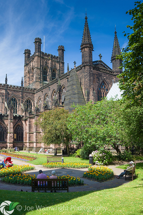 Visitors to the city enjoy summer sunshine in the grounds of Chester Cathedral.  the building originated as a Benedictine monastery in 1093 and some parts of the structure date from that time.