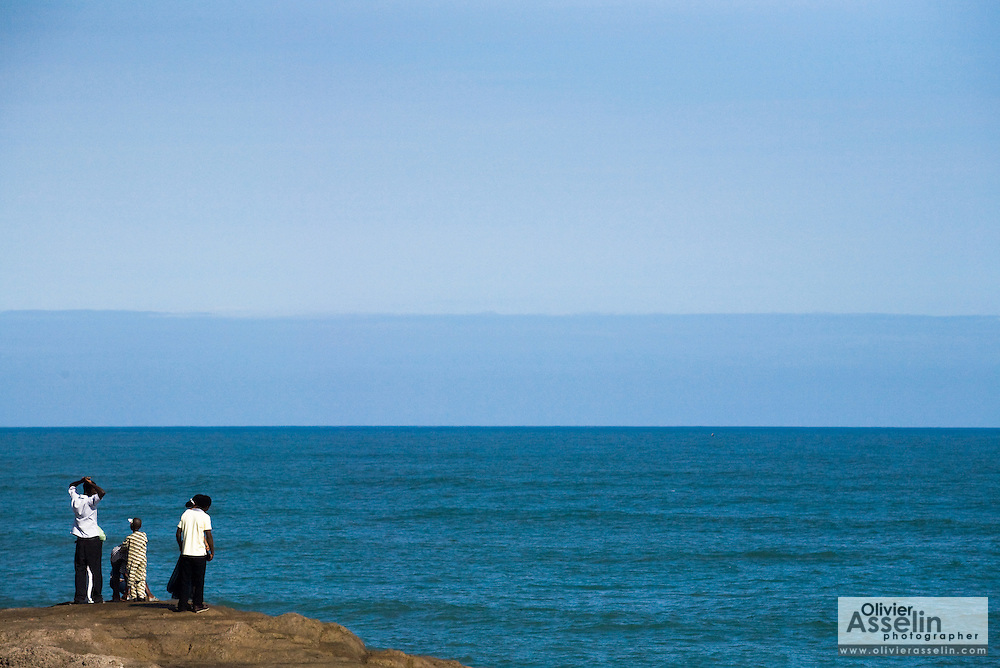 A group of people enjoy a view of the ocean in Cape Coast, Ghana on Saturday September 6, 2008.