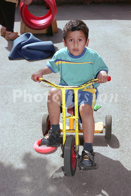 Nursery school boy riding tricycle around playground,