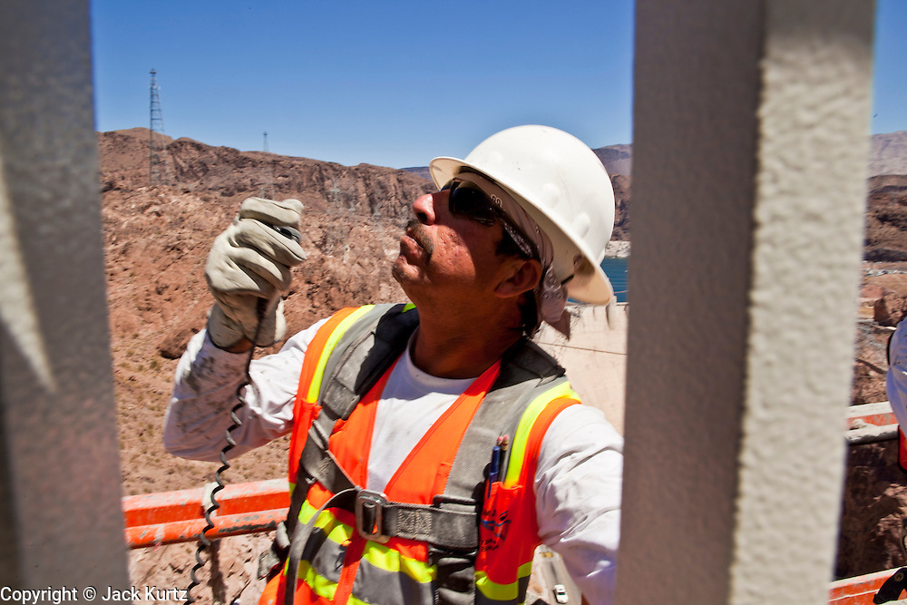 19 AUGUST 2010 --  HOOVER DAM, AZ: Gus Gomez, from Obayashi, uses his radio to talk to a crane operator on the Hoover Dam By pass bridge.  Construction work is continuing on the Hoover Dam bypass bridge. The Colorado River Bridge is the central portion of the Hoover Dam Bypass Project. Construction on the nearly 2,000 foot long bridge began in late January 2005 and the completion of the entire Hoover Dam Bypass Project is expected in late 2010.  When completed, this signature bridge will span the Black Canyon (about 1,500 feet south of the Hoover Dam), connecting the Arizona and Nevada Approach highways nearly 900-feet above the Colorado River. PHOTO BY JACK KURTZ