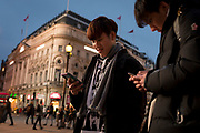 Two foreign phone users check messages in front of the Trocadero in Piccadilly Circus, on 22nd November 2019, in Westminster, London, England.