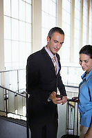 Business man showing woman mobile phone in airport lobby