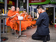 01 JANUARY 2017 - BANGKOK, THAILAND:         A Big C store employee kneels in front of Buddhist monks during a merit making ceremony at a Big C grocery store in central Bangkok. Thais traditionally go to temples to pray and make merit on New Year's Day. There are also large merit making ceremonies in many towns. Many Thai businesses ask Buddhist monks to come to their businesses for merit making ceremonies on New Year's Day.      PHOTO BY JACK KURTZ
