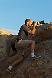 Photographer with telephoto lens standing on a large rock, Alabama Hills, Lone Pine, California, United States of America