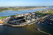 Nederland, Gelderland, Nijmegen, 24-10-2013. Noordkanaalhaven, gelegen aan de kruising van de Waal en het Maas-Waalkanaal. Containerterminal en overslag van kolen.<br /> Bruggen De Snelbinder en De Oversteek.<br /> Nederland, Gelderland, Nijmegen, 24-10-2013. Noordkanaalhaven, gelegen aan de kruising van de Waal en het Maas-Waalkanaal. Containerterminal en overslag van kolen.<br /> <br /> Port in Nijmegen (central Netherlands), container terminal and transshipment of coal . The river Waal and its bridges.<br /> <br /> luchtfoto (toeslag op standaard tarieven);<br /> aerial photo (additional fee required);<br /> copyright foto/photo Siebe Swart.