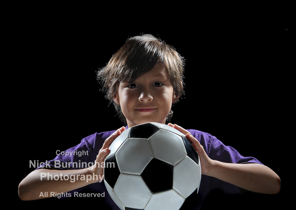 Dramatic back-lit boy with soccer ball on black background