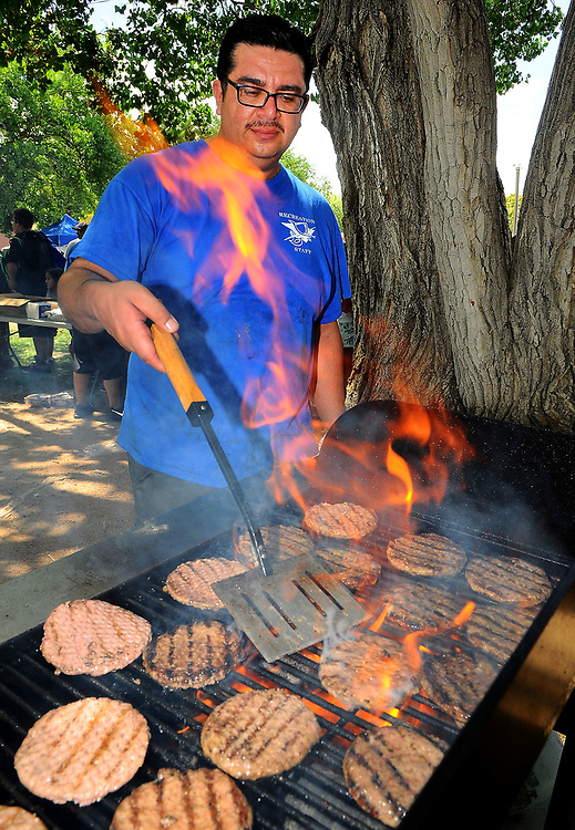 jt071417f/ a sec/jim thompson/Recreation Director for the Town of Bernalillo, Jason Soto cooks burgers for the crowd of kids and parents  at Rotary Park in Bernalillo,NM  as they attend the Cops in the Park celebration. Friday,  July. 14, 2017. (Jim Thompson/Albuquerque Journal)