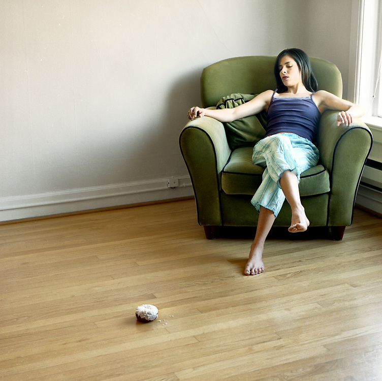 Young woman, 20's something, sitting in chair looking at a donut on the floor of living room
