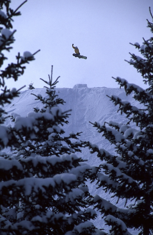 A Snowboarder flies off a jump framed by trees. Papova Shopka, Macedonia
