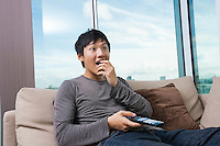 Surprised mid-adult man watching television on sofa at home