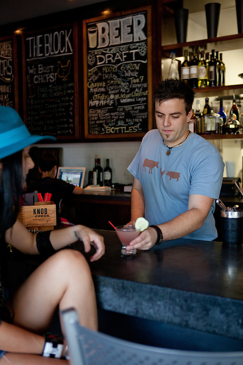 A bartender serves a cocktail to a patron of The Block Restaurant in Webster Groves in St. Louis, MO.