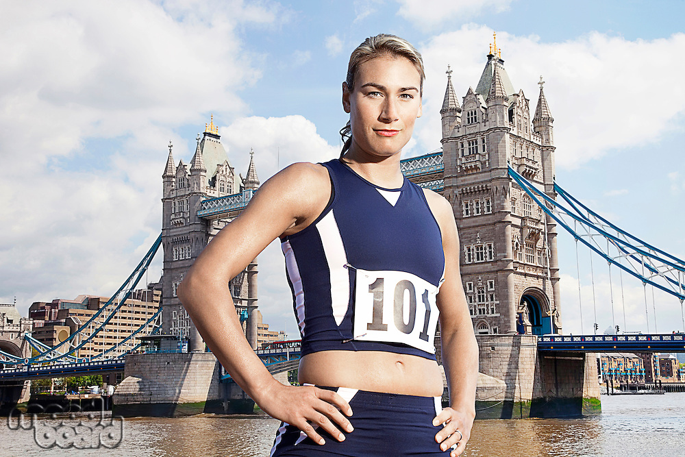 Female Athlete standing in front of Tower Bridge