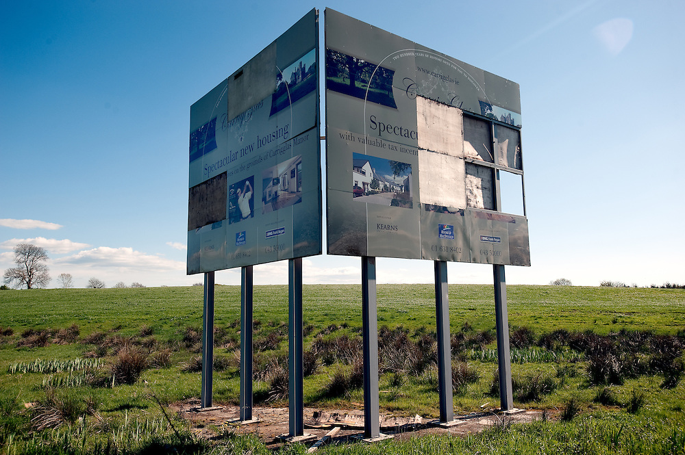 "A damaged billboard on the outskirts of Longford town advertises ""Carrig Glas"". Launched in 2006 by the then minister for finance Brian Cowen and golfer Retief Goosen, the EUR160 million development, set on 660 acres was to consist of a world championship golf course, a 96 bedroom hotel, a spa, country club and over 300 properties that were priced from EUR350,000 to EUR500,000. Construction work stopped in 2007 and has yet to resume."