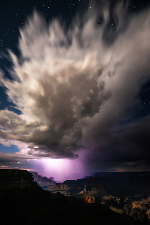 Rain falling from a summer thunderstorm is backlit by lightning, stars are visible in the night sky above the storm, and the canyon is lit by a nearly full moon. Photographed at Grand Canyon National Park in the summer of 2012.