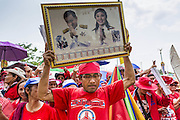 April 6, 2014 - Bangkok, Bangkok, Thailand - <br /> <br /> Red Shirts Rally in Bangkok Suburbs<br /> <br /> A man holds up photos of Thaksin Shinawatra, the exiled former Prime Minister of Thailand and Yingluck Shinawatra, the current Prime Minister and Thaksin's sister. Red Shirts and supporters of the government of Yingluck Shinawatra, the Prime Minister of Thailand, gathered in a suburb of Bangkok this weekend to show support for the government. The Thai government is dealing with ongoing protests led by anti-government activists. Legal challenges filed by critics of the government could bring the government down as soon as the end of April. The Red Shirt rally this weekend was to show support for the government, which public opinion polls show still has the support of most of the electorate.<br /> ©Exclusivepix