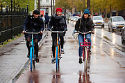 Drie meisjes fietsen in de regen door Amsterdam.<br /> <br /> Three girls cycles in the rain in Amsterdam.