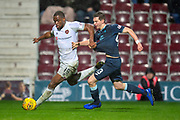 Uche Ikpeazu (#19) of Heart of Midlothian holds off Steven Saunders (#43) of Partick Thistle FC during the William Hill Scottish Cup quarter final replay match between Heart of Midlothian and Partick Thistle at Tynecastle Stadium, Gorgie, Edinburgh Scotland on 12 March 2019.