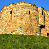 Clifford's Tower in York, England<br /> Two years after William the Conqueror became the first Norman king of England in 1066, he commissioned a wooden, motte-and-bailey castle be built in York. Within a year it was destroyed by the Vikings.  Not to be deterred, William I had it rebuilt with greater fortifications including a moat.  When King Henry III reconstructed it again during his reign from 1216 through 1272, this limestone keep was added. Master Mason Henry de Rayns gave it a unique design with four semi-circles called quatrefoil. It was originally called King's Tower. It was renamed as a tribute to Henry Clifford, 5th Earl of Cumberland.  His Royalist forces defeated the Parliamentarians here in 1643 while defending the throne of King Charles I. This medieval landmark atop a motte in center city is one of the few structures remaining of York Castle.