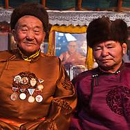 Mongolia. Ulaanbaatar. portrait in Adia family with traditional mongol dress, the Del.  with their medals. in the yurt area of the capital , grand father, grand mother and sohn  Ulan Baatar -   / portrait de La famille Adia, couverte de madaille. habille du vetement traditionel le Del,  dans le quartier de yourte de la capitale, les grands parents avec enfants et petis enfants  Oulan Bator - Mongolie